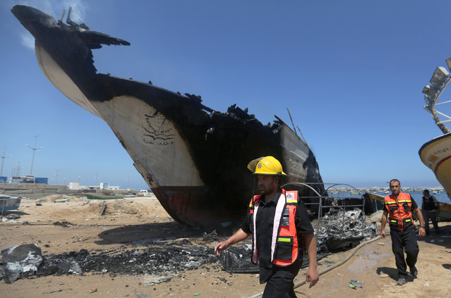 Palestinian firefighters walk around a boat hit in an missile strike at the port in Gaza City, Friday, July 11, 2014. (Photo by Hatem Moussa/AP Photo)