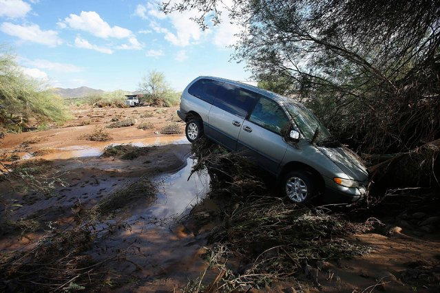 A vehicle sits atop debris where flash flood waters pushed it after rising waters overran Skunk Creek after strong storms moved through, Tuesday, August 19, 2014, in New River, Ariz., just northwest of Phoenix. Heavy monsoon season rains that swept across Arizona on Tuesday led to dramatic rescues, road closures and flight delays as a series of fast-moving storms pummeled the state. (Photo by Ross D. Franklin/AP Photo)