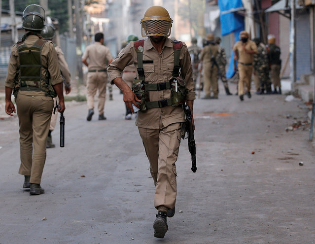 An Indian policeman runs during a protest in Srinagar against the recent killings in Kashmir, July 18, 2016. (Photo by Danish Ismail/Reuters)