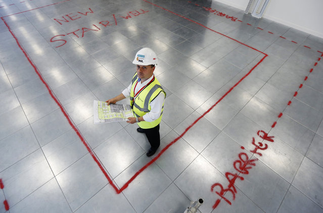 Senior construction manager Paul Barker poses on site during an office renovation project in the Canary Wharf business district in London July 16, 2014. (Photo by Luke MacGregor/Reuters)