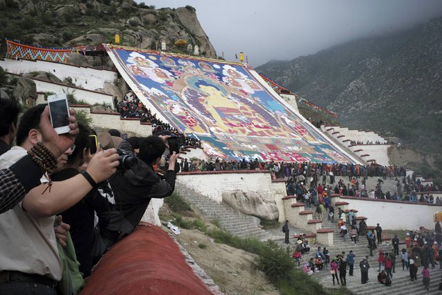 Tibetan Buddhists and tourists view a huge Thangka, a religious silk embroidery or painting displaying a Buddha portrait, during the Shoton Festival at Zhaibung Monastery in Lhasa, capital of southwest China's Tibet Autonomous Region, August 25, 2014. (Photo by Reuters/China Daily)