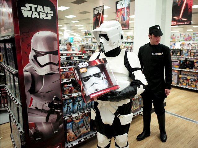 """Star Wars fans dressed as an Imperial Stormtrooper (L) and Admiral look at merchandise from the upcoming film """"Star Wars: The Force Awakens"""" just before midnight on """"Force Friday"""" in Sydney, September 4, 2015. (Photo by Jason Reed/Reuters)"""