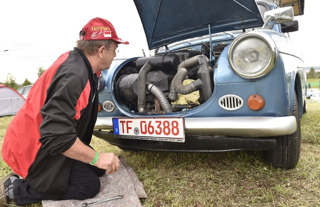 A car driver repairs the 23 horse power engine of his Trabant 500 car as fans of the East German Trabant car gather for their 7th annual get-together on August 23, 2014 in Zwickau, Germany. Hundreds of Trabant enthusiasts arrived to spend the weekend admiring each others cars, trading stories and enjoying activities. The Trabant, dinky and small by modern standards, was the iconic car produced in former communist East Germany and today has a strong cult following. (Photo by Matthias Rietschel/Getty Images)