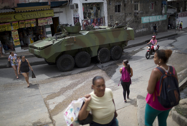 Residents walk past an armored vehicle at the Rocinha favela, in Rio de Janeiro, Brazil, Saturday, September 23, 2017. Shootouts erupted in several areas of Rio de Janeiro on Friday, prompting Brazilian authorities to shut roads, close schools and ask for the Army to intervene. (Photo by Silvia Izquierdo/AP Photo)