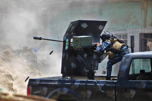 """An Iraqi forces member fires a 23 mm anti-aircraft gun as they advance towards the Old City of Mosul on June 19, 2017 during an ongoing offensive to retake the last district still held by the Islamic State (IS) group fighters. Iraqi forces pushed deeper into Mosul's Old City after launching a final assault on the Islamic State group, warning civilians to stay inside and telling jihadists to """"surrender or die"""". (Photo by Ahmad Al-Rubaye/AFP Photo)"""