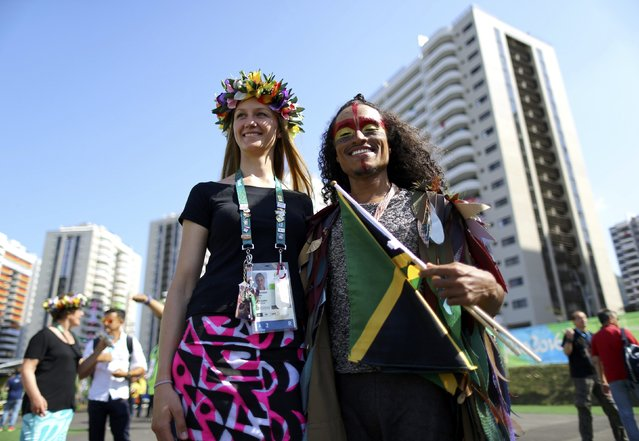 Sailor Teau Moana McKenzie (COK) of Cook Islands (L) poses with a dancer during the welcoming ceremony for the country's contingent in Rio de Janeiro, Brazil on August 4, 2016. (Photo by Ivan Alvarado/Reuters)