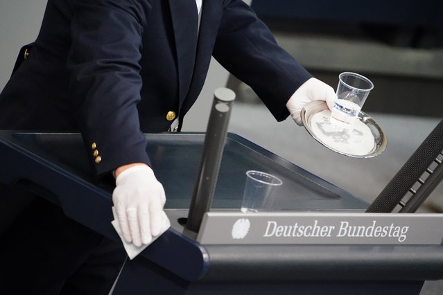 An usher cleans the speaker's desk in between speeches during a session of the German parliament 'Bundestag' in Berlin, Germany, 15 May 2020. The German parliament will discuss the global humanitarian situation amid the coronavirus crisis, among other topics. (Photo by Clemens Bilan/EPA/EFE)