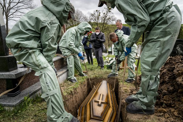 In this photo taken on Saturday, May 2, 2020, funeral workers, wearing protective suits, lower the coffin of Semen Muchka, 71, who died of coronavirus disease, into the grave at a cemetery in Krynytsya, Ukraine. (Photo by Evgeniy Maloletka/AP Photo)