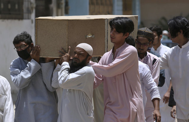 People carry the casket of a victim of Friday's plane crash, for funeral prayers in Karachi, Pakistan, Saturday, May 23, 2020. An aviation official says a passenger plane belonging to state-run Pakistan International Airlines carrying passengers and crew has crashed near the southern port city of Karachi. (Photo by Fareed Khan/AP Photo)