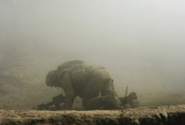 A wounded Canadian soldier from the NATO-led coalition crawls for cover seconds after his position was hit by a Taliban shell fired from an 82-millimeter recoilless rifle during an ambush in Zhari district of Kandahar province, southern Afghanistan, October 23, 2007. One Canadian soldier was lightly wounded and an Afghan National Army soldier was shot in the shoulder during heavy fighting in the volatile Mowz-e-Madad area of Kandahar province. (Photo by Finbarr O'Reilly/Reuters)