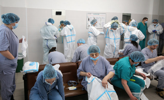 """Staff members put on protective suits before entering the """"red zone"""" of a temporary medical facility established for COVID-19 patients at Moscow City Clinical Hospital No 15 (Filatov Hospital) in Moscow, Russia on May 29, 2020. (Photo by Sergei Bobylev/TASS)"""