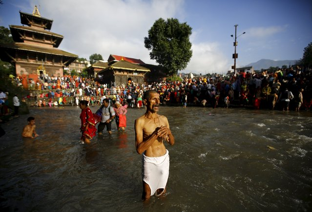 A Hindu devotee performs a ritual on Bagmati River during Kuse Aunse (Father's Day) at Gokarna Temple in Kathmandu, Nepal September 13, 2015. (Photo by Navesh Chitrakar/Reuters)