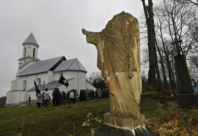 Belarus Catholics take part in a procession marking All Saints' Day at a cemetery in the village of Vselyub, 150 km (93 miles) west of Minsk, Wednesday, November 1, 2017. Belarusian Catholics marked All Saints Day by visiting graves of their relatives. (Photo by Sergei Grits/AP Photo)