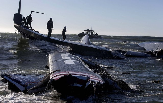 Crew members of the capsized Oracle Team USA AC72 boat are rescued after being swept past the Golden Gate Bridge in San Francisco. (Photo by Guilain Grenier/Oracle Team USA)