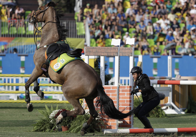 Haydy Morsy of Egypt reacts after falling from the horse as she competes at the equestrian section of the women's modern pentathlon at the Summer Olympics in Rio de Janeiro, Brazil, Friday, August 19, 2016. (Photo by Natacha Pisarenko/AP Photo)