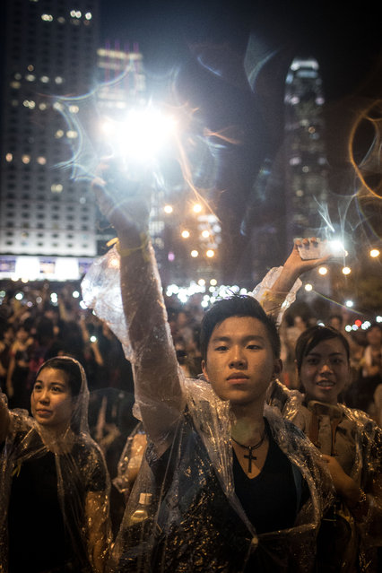 Protesters sing songs and wave their cell phones in the air after a massive thunderstorm passed over outside the Hong Kong Government Complex on September 30, 2014 in Hong Kong, Hong Kong. (Photo by Paula Bronstein/Getty Images)