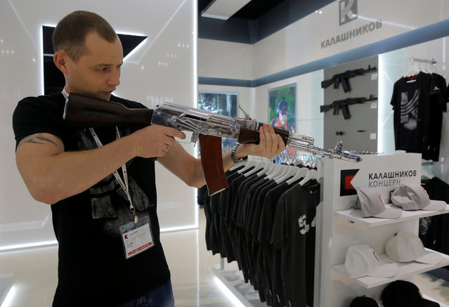 A salesperson demonstrates a model AK-47 assault rifle at the newly opened Gunmaker Kalashnikov souvenir store in Moscow's Sheremetyevo airport, Russia, August 22, 2016. (Photo by Maxim Shemetov/Reuters)