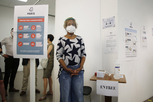 A woman wearing a face mask and visor to protect against coronavirus stands at the entrance of a polling station during a rehearsal of the vote for the local elections scheduled for Sunday, June 28, in Paris, Friday, June 26, 2020. France is to hold its Covid-19 delayed second round of local elections on June 28. (Photo by Thibault Camus/AP Photo)