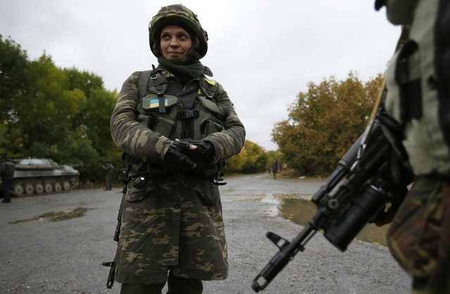 """Ukrainian servicewoman Nadie, 36, stands at the military camp in the village of Luhanske, eastern Ukraine September 24, 2014. Before fighting broke out in eastern Ukraine, Irina was a croupier in a casino who never dreamt of taking up arms. Now she is gambling with her life. Using the nom de guerre """"Gaika"""". (Photo by David Mdzinarishvili/Reuters)"""