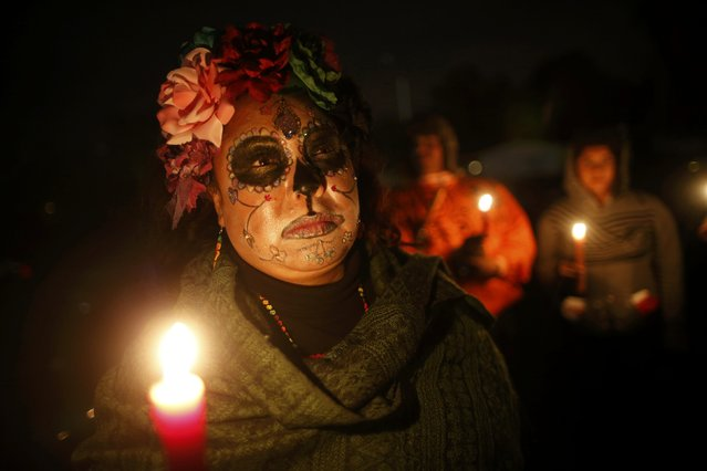 Letitia Seitz holds a candle at a vigil for Michael Brown and Latinos that have been killed by police, in Ferguson, Missouri, October 10, 2014. Civil rights organizations and protest groups have invited people from around the country to join vigils and marches from Friday to Monday over the Aug. 9 shooting of Michael Brown, 18, in the St. Louis suburb of Ferguson. (Photo by Jim Young/Reuters)