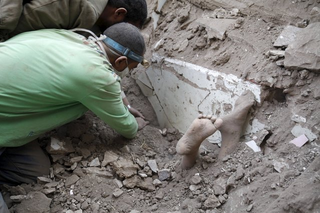 The feet of a child covered in dust are seen as people search for survivors under the rubble of a house destroyed by an air strike at the old quarter of Yemen's capital Sanaa, September 19, 2015. (Photo by Mohamed al-Sayaghi/Reuters)