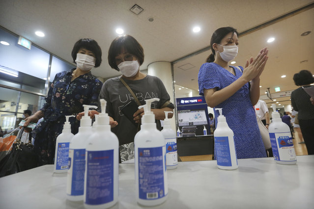 Christians wearing face masks to help protect against the spread of the new coronavirus use hand sanitizer before attending a service at the Yoido Full Gospel Church in Seoul, South Korea, Sunday, July 5, 2020. (Photo by Ahn Young-joon/AP Photo)