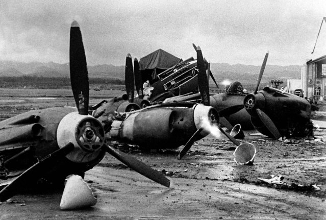 The shattered wreckage of American planes bombed by the Japanese in their attack on Pearl Harbor is strewn on Hickam Field, December 7, 1941. (Photo by Associated Press)