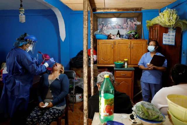 A healthcare worker wearing personal protective equipment (PPE) conducts a test to a patient while going house to house to test people for the coronavirus disease (COVID-19) in the municipality of Tlahuac, one of the highly contagious zone of Mexico City, as the coronavirus disease (COVID-19) outbreak continues in Mexico on July 20, 2020. (Photo by Carlos Jasso/Reuters)