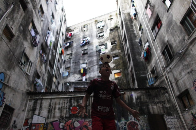 A member of Brazil's Movimento dos Sem-Teto (Roofless Movement) plays with a soccer ball in the courtyard of one of the 11 empty buildings that the movement took over recently, in the centre of Sao Paulo, November 18, 2012. According to City Hall, there are some 400,000 people in need of stable housing, including the 4,000 families of the Roofless Movement who are squatting in abandoned or vacant buildings that range from apartment blocks to hotels, in Sao Paulo, the largest city in South America. Picture taken November 18, 2012