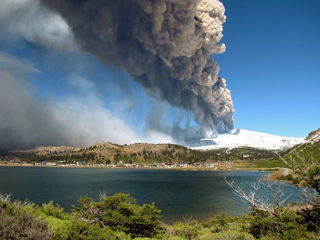 View of the Copahue volcano spewing ashes behind the lagoon of Caviahue, Neuquen province, Argentina, some 1500 km southwest of Buenos Aires on December 22, 2012. The authorities of Chile and Argentina issued yellow alerts due to the eruption of the Copahue volcano, placed in the border between both countries. (Photo by Antonio Huglich/AFP Photo)