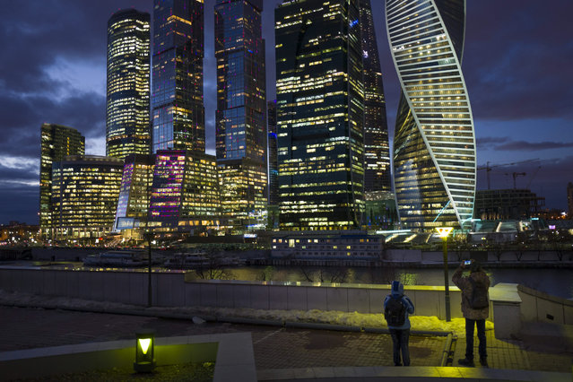 People take photos of skyscrapers in the Moscow City across the Moskva River in Moscow, Russia, Thursday, February 4, 2016. (Photo by Alexander Zemlianichenko/AP Photo)