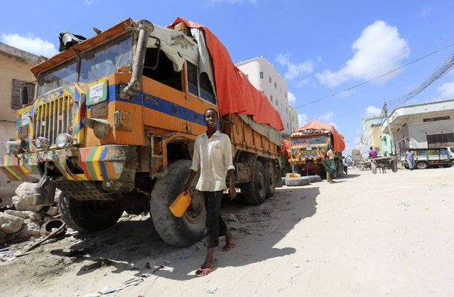 A boy walks past trucks loaded with cleared imported goods near the sea port in Somalia's capital Mogadishu October 23, 2014. The Somali government's grand vision for Mogadishu port under its new Turkish managers sees modern container ships replacing wooden dhows, new cranes easing the back-breaking work of porters and a surge in state revenue as traffic rises. (Photo by Feisal Omar/Reuters)