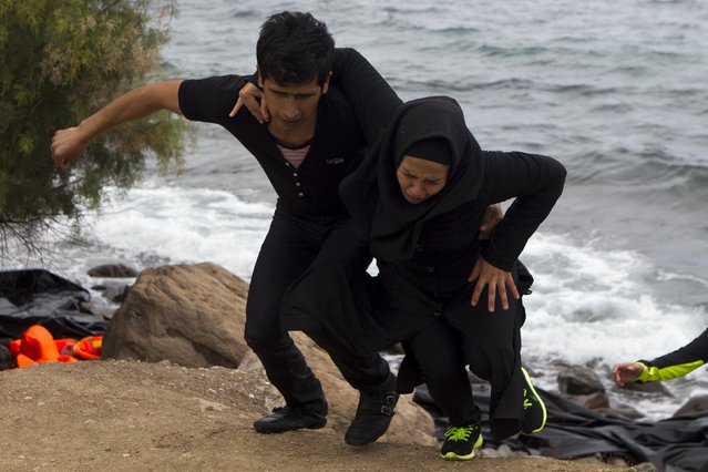 A migrant (L) helps a woman to climb a slope following their arrival on the Greek island of Lesbos, after crossing a part of the Aegean Sea from the Turkish coast, September 30, 2015. A record number of at least 430,000 refugees and migrants have taken rickety boats across the Mediterranean to Europe this year, 309,000 via Greece, according to International Organization for Migration figures. (Photo by Dimitris Michalakis/Reuters)