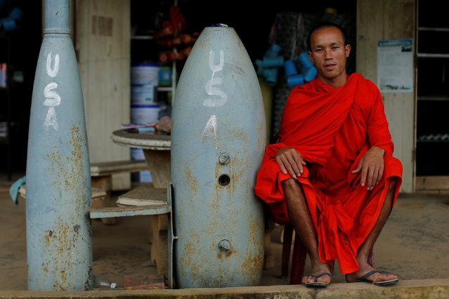 A Buddhist monk poses next to unexploded bombs dropped by the U.S. Air Force planes during the Vietnam War, in Xieng Khouang in Laos September 3, 2016. (Photo by Jorge Silva/Reuters)