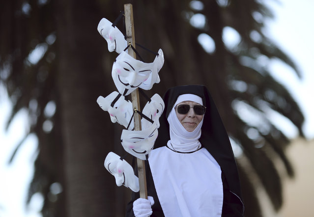 A protester dressed as a nun holds Guy Fawkes masks during a demonstration in San Francisco, California November 5, 2014. (Photo by Robert Galbraith/Reuters)