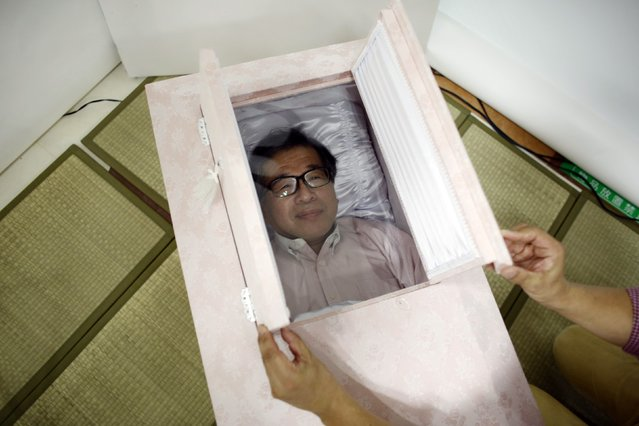 Yoshiya Yoshimura lies in a coffin to try it out during an end-of-life seminar held by Japan's largest retailer Aeon Co in Tokyo October 24, 2014. (Photo by Toru Hanai/Reuters)