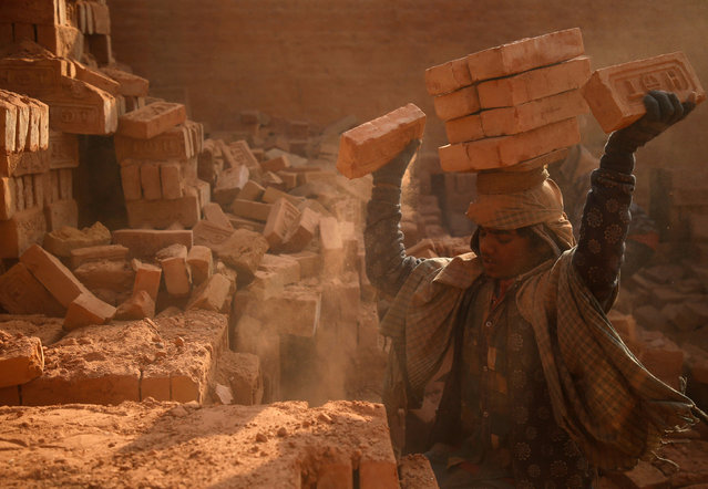 A worker stack bricks on his head at a brick factory in Bhaktapur, Nepal January 12, 2018. (Photo by Navesh Chitrakar/Reuters)