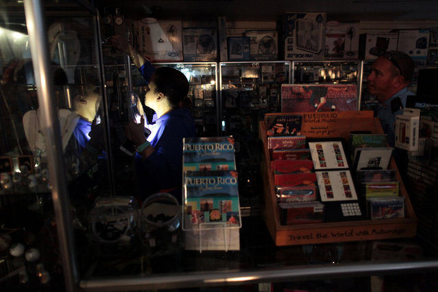 The employee of a drug store attends to a client during a power outage after a fire at an energy plant knocked out electricity for the bulk of the island, in San Juan, Puerto Rico, September 22, 2016. (Photo by Alvin Baez/Reuters)