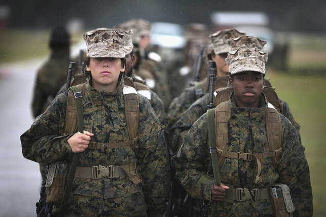 Female Marine recruits prepare to fire on the rifle range during boot camp February 25, 2013 at MCRD Parris Island, South Carolina. All female enlisted Marines and male Marines who were living east of the Mississippi River when they were recruited attend boot camp at Parris Island. About six percent of enlisted Marines are female. (Photo by Scott Olson/AFP Photo)