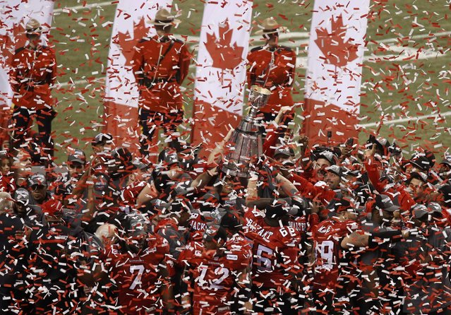 Calgary Stampeders players hold up a broken Grey Cup as they celebrate defeating the Hamilton Tiger Cats in the CFL's 102nd Grey Cup football championship in Vancouver, British Columbia, November 30, 2014. (Photo by Ben Nelms/Reuters)