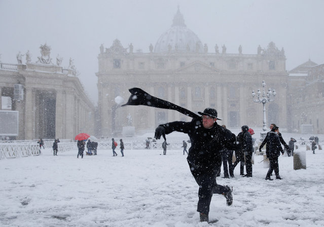 A young priest throws a snow ball during a heavy snowfall in Saint Peter's Square at the Vatican on February 26, 2018. Snow in Rome disrupts transport, shuts down schools and prompts authorities to call in the army to help clear the streets. (Photo by Max Rossi/Reuters)