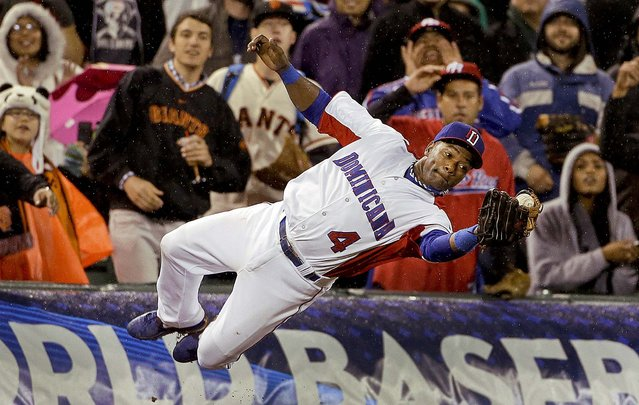 The Dominican Republic's Miguel Tejada (4) catches a foul ball hit by Puerto Rico's Jesus Feliciano during the seventh inning of the championship game of the World Baseball Classic in San Francisco, on March 19, 2013. The Dominicans won 3–0. (Photo by Eric Risberg/Associated Press)