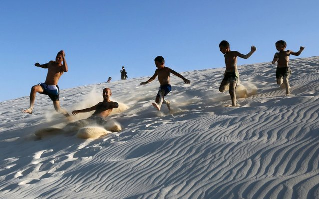 People slide down a dune at the beach in Marsa Matruh, some 500 km northwest of Cairo, Egypt, 27 August 2020. (Photo by Khaled Elfiqi/EPA/EFE/Rex Features/Shutterstock)