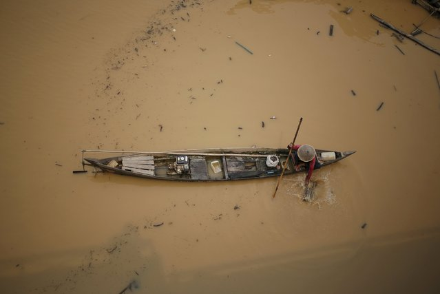 A fisherman checks is trap on the Kahayan River after intermittent rainfall over the last few days cleared away the heavy haze which blanketed the city of Palangkaraya, Central Kalimantan, Indonesia October 29, 2015. Indonesia's weather agency failed to predict that the effects of the El Nino weather phenomenon this year would be worse than in 1997, a senior minister said on Wednesday, as the government considers declaring a national emergency due to forest fires. (Photo by Darren Whiteside/Reuters)