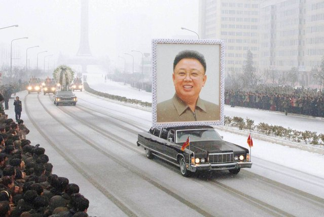 In this photo taken on December 28, 2011 a car carries a portrait of Kim Jong-Il during the funeral procession in Pyongyang. Millions of grief-stricken people turned out to mourn Kim Jong-Il, whose death has left the world scrambling for details about his young successor. (Photo by Reuters/Kyodo)