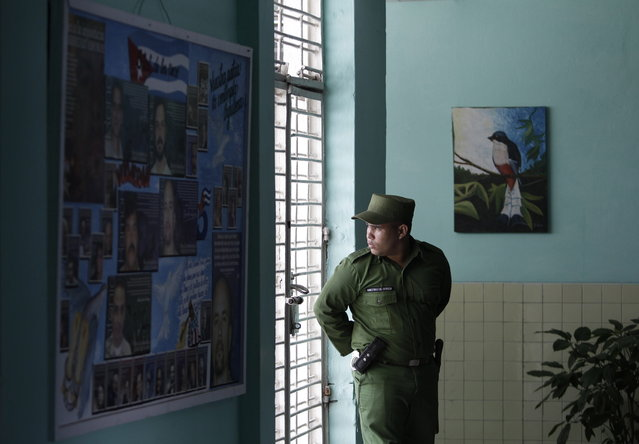 A military guard looks through the window from inside the medical clinic at the Combinado del Este prison during a media tour in Havana, Cuba, Tuesday, April 9, 2013. Cuban authorities led foreign journalists through the maximum security Eastern Combined, the largest prison in the Caribbean country that houses 3,000 prisoners. Cuba says they have 200 prisons across the country, including five that are maximum security. (Photo by Franklin Reyes/AP Photo)
