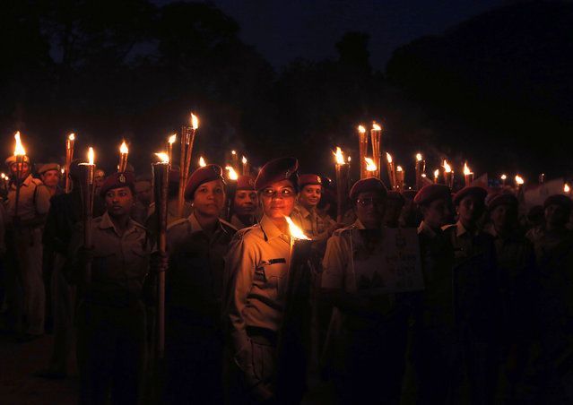 Female members of the Indian Home Guard hold torches during a march to mark the 68th Raising Day of the Indian Home Guards celebrations in the western Indian city of Ahmedabad December 6, 2014. The Indian home guard is an auxiliary to the police. (Photo by Amit Dave/Reuters)