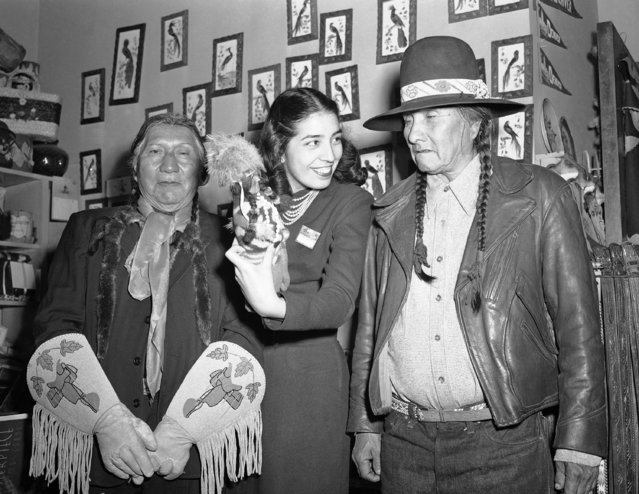 These three delegates to the American Indian congress at Denver took time between sessions Tuesday, December 14, 1948 to do some Christmas looking in the hotel curio shop. They seemed to find mild amusement in this Indian doll. From Left to right are: John Pawinnee, 78, Ute from Fort Duchesne, Utah; Susan Kelly Sioux, and Jack House, 66, Mountain Ute from Towaoc, Colo. Those gloves Pawinnee seems so proud of were made by his wife. They are buckskin, decorated miniature saddles in bead work. (Photo by AP Photo)