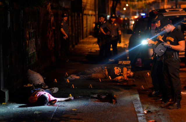 "Police investigators inspect the bodies of two men lying on a sidewalk, who police said were killed after a drug ""Shabu"" (Methamphetamine Chloride) buy-bust operation in Quezon city, Metro Manila Philippines, October 9, 2016. (Photo by Ezra Acayan/Reuters)"