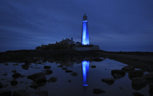 St Mary's lighthouse in Whitley Bay on the North East coast is illuminated blue in recognition and support of NHS workers and carers fighting the coronavirus pandemic on April 17, 2020. (Photo by Owen Humphreys/PA Images via Getty Images)